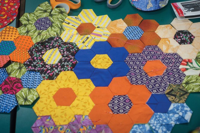 """""""We kind of looked at the little hexagons as pixels,"""" says Lillis Taylor, a textile artist, quilter and artist-in-residence for UAB Arts in Medicine. She used these geometric shapes, or """"hexies,"""" to design two quilts with images of a mother and baby, and a nurse with an elderly patient. (UAB photo/Steve Wood)"""