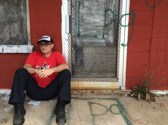 Huntsville musician Michael Kilpatrick is seated outside the front door of the old Tip Top building at 123 Maple Ave. (Matt Wake/mwake@al.com)