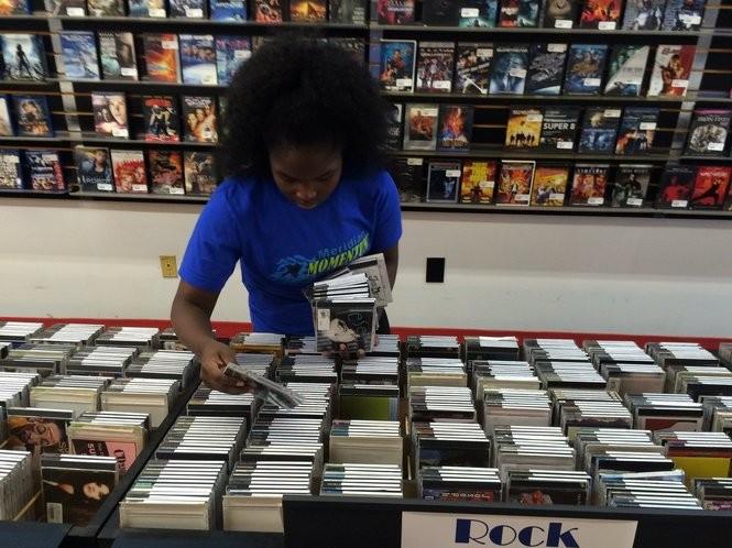 The Exchange employee Shawnda Gaines goes through some of the store's CD racks. (Matt Wake/mwake@al.com)