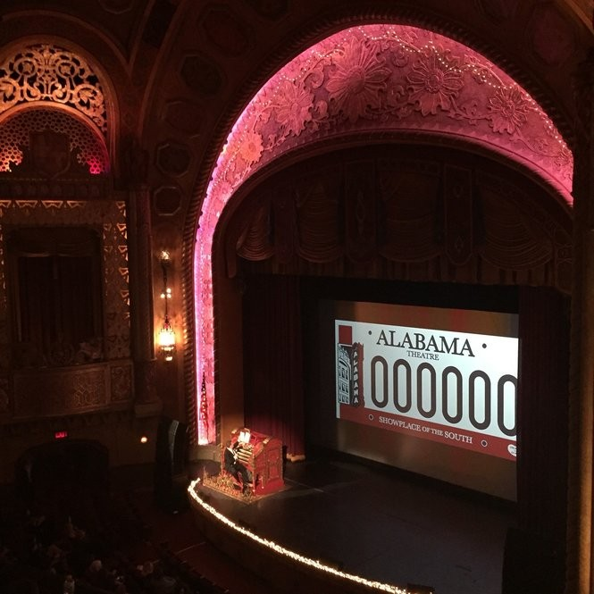 Before one of the Christmas movies at the Alabama Theatre, house organist Gary Jones encourages patrons to show their love for the theater by purchasing a specialty car tag. (Photo by Glenny Brock)