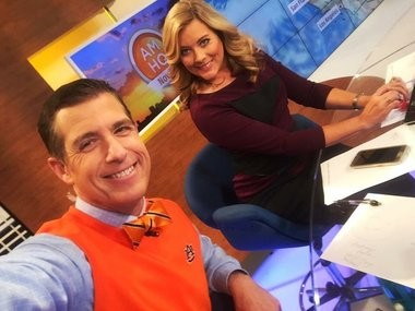 Reynolds Wolf wearing an Auburn sweater vest and trademark bowtie in the Weather Channel studio with meteorologist Kelly Cass before the 2016 Auburn-Georgia game.