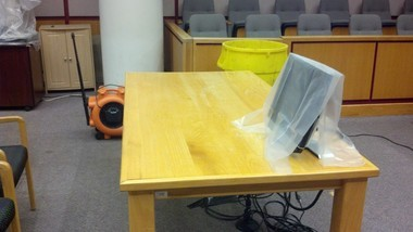 Mobile County Circuit Judge Michael Youngpeter's courtroom leaked water from the ceiling on Thursday, May 2, 2013. In this picture, a yellow trash can has been placed by the jury box to catch water, a wet-dry vac is sucking water from the carpet and a monitor has been covered with plastic. (Brendan Kirby/bkirby@al.com)