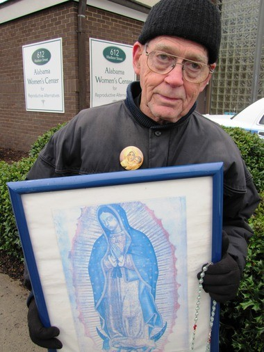 Brother Joseph Kreutzer holds a poster of Our Lady of Guadalupe, a vision of the pregnant Mary who is considered the guardian of the unborn, as he demonstrates outside the Alabama Women's Center for Reproductive Choices in Huntsville, Ala., on Wed., Jan. 16, 2013. Kruetzer, a regular outside the clinic on Wednesday afternoons and Saturdays, says he has marched and prayed to try to prevent abortions for the last 15 years. (Kay Campbell / kcampbell@al.com)