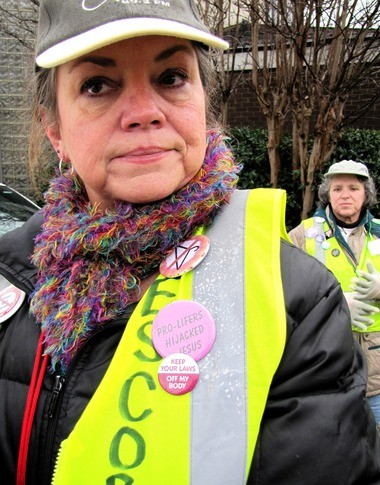 """Pamela Watters, one of the leaders of pro-choice activists who volunteer Wednesdays and Saturdays outside Alabama Women's Center for Reproductive Alternatives in Huntsville, wears buttons that help summarize her positions. The bloody coat hanger icon refers to activists' determination that the U.S. not return to the days of back-alley abortions that happened when abortions were outlawed in the country. """"Pro-lifers hijacked Jesus"""" protests the simplification that all Christians are oppose keeping abortions, as Watters puts it, """"safe, legal, and rare."""" (Kay Campbell / kcampbell@al.com)"""