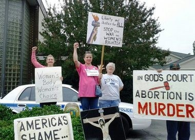 Conflicting certainties broadcast from the posters held by protestors outside Huntsville's Alabama Women's Center for Reproductive Alternatives. This photo was taken during October 2012. (Courtesy of Will Henley)