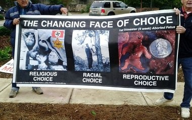 While some pro-life protestors carry signs offering help and urging the choice of life, others graphically depict the category into which some class a decision to have an abortion. This is among signs regularly carried outside Huntsville's Women's Center for Reproductive Alternatives. (Courtesy of Will Henley).