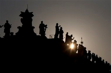 The sun sets behind the statues on top of the Bernini colonnade in St. Peter Square, at the Vatican, Monday, March 4, 2013. (AP photo/Andrew Medichini)