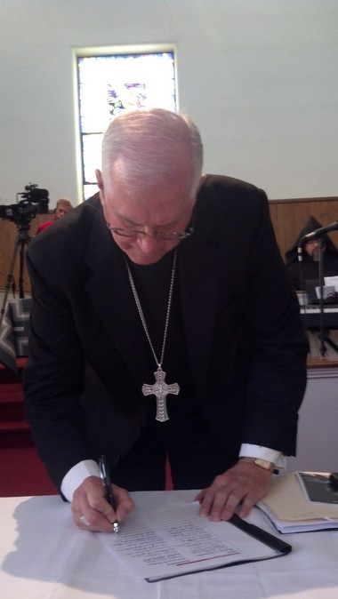 "Catholic Archbishop Joseph E. Kurtz of Louisville, Ky., signs a response to the Rev. Martin Luther King Jr.'s ""Letter From Birmingham Jail,"" April 15, 2013, at St. Paul United Methodist Church in Birmingham, Alabama. (Photo by Greg Garrison/ggarrison@al.com)"