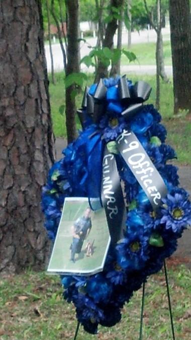 Memorial flowers displayed at the grave shows Patrol Officer David Sheppard with Gunnar. (Nathan Prewett/NPrewett@al.com)