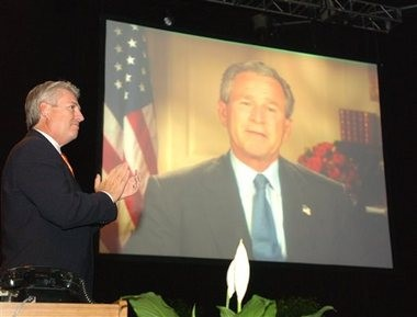 In this Tuesday, June 15, 2004, file photo, Dr. Jack Graham, outgoing president of the Southern Baptist Convention, applauds a video address by President George W. Bush at the annual meeting of the Southern Baptist Convention at the Indiana Convention Center in Indianapolis. (AP Photo/Tom Strickland, File)