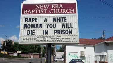 The flip side of the sign refers to a 1983 rape case for which the three black assailants are still serving time in prison. (Photo by Greg Garrison/ggarrison@al.com)