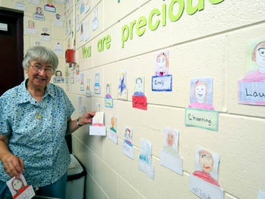Sister Joan Wagner, a Salvatorian missionary, puts up a bulletin board in the entry way of Holy Family Catholic School that celebrates the many hues of the faces of the school's students. (Kay Campbell / KCampbell@AL.com)