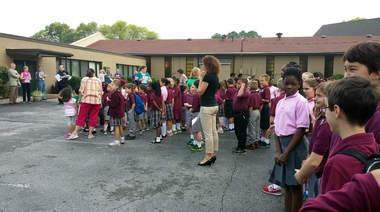 Students, staff, friends and alumni of Holy Family Catholic School and St. Joseph's Catholic School, gather the morning of Tuesday, Sept. 3, 2013, at the school to pray together for peace in honor of the 50th anniversary of the racial segregation of the school, started in 1956 as a mission to African-American children in Huntsville and integrated in 1963 when white Catholic students applied for admission and started classes. (Courtesy of Stephanie Shaw)
