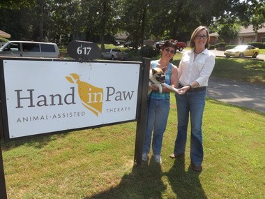 Kim Dillenbeck, holding Pig, along with Laura Cardwell, executive director of Hand in Paw Animal Assisted Therapy. (Photo by Joey Kennedy)