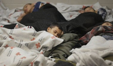 Children sleep in a holding cell at a U.S. Customs and Border Protection processing facility in Brownsville, Texas, on June 18, 2014. (AP Photo)