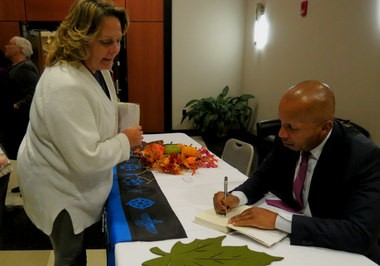 Lawyer Bryan Stevenson, a nationally known advocate for people who have been wrongly convicted of crime, signs a copy of his book, 'Just Mercy,' for Marsha Colbey, who spent 12 years in Alabama's Tutwiler Prison on a conviction of murdering her child - a conviction that was overturned once she got a fair trial. Stevenson's talk opened the 2014 Exploring Faith Intersections, a conference organized by the Interfaith Mission Service in Huntsville, Ala., Nov. 2-3, 2014. (Kay Campbell/KCampbell@AL.com)