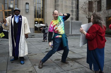 The Rev. Herman Henderson, left, pastor of Believers' Temple, preached against homosexuality as gay couples came out of the Jefferson County Courthouse with their marriage licenses on Monday, Feb. 9, 2015. The Rev. Dave Barnhart, pastor of St. Junia United Methodist Church, right, got up in front of Henderson and began dancing. (Photo by Tamika Moore/AL.com)