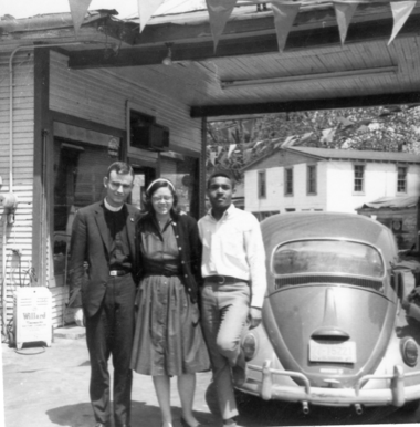 A 1965 photo of Jonathan Daniels with fellow activists Judy Upham and Ron Fuller at a Selma gas station. Fuller was a student activist at R. B. Hudson High School. Upham lent a red Volkswagen to Jonathan to drive as he registered voters during the voting rights campaign. Judy was also a student at the Episcopal Theological School in Cambridge, Massachusetts, and became one of the first women Episcopal priests.