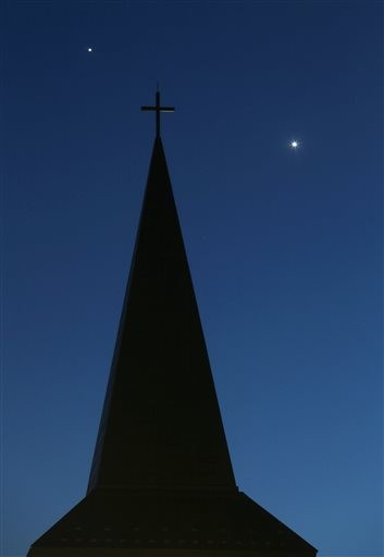 The planets Venus, right, and Jupiter share the evening sky behind St. Jerome's Catholic Church in Oconomowoc, Wis. Tuesday, June 23, 2015. (John Hart/Wisconsin State Journal via AP)