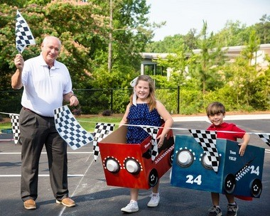 In lieu of a traditional ribbon-cutting ceremony, Vestavia Hills High School Head Football Coach Buddy Anderson and Mary Catherine and Jack Morrow celebrate the opening of the Library in the Forest's expanded parking lot by racing to break through the finish line. (Contributed)