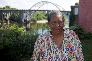 Joanne Bland stands in front of the Edmund Pettus Bridge in Selma. Bland was the youngest marcher on Bloody Sunday at just 11 years old. She now revisits the bridge when she gives historical tours of Selma. (Jeffrey Pierre/News21)