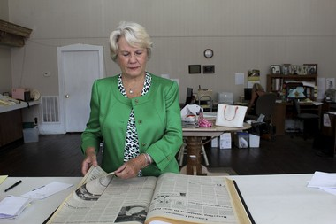 Clayton Mayor Rebecca Beasley flips through an archive of issues of the Clayton Record in the newspaper's downtown office. Beasley's family has owned the newspaper since 1915. (Phillip Jackson/News21)