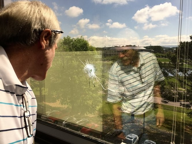 University of Alabama in Huntsville climate scientist Dr. John Christy looks at a bullet hole in the window of the office next to his at the university. Seven shots were fired at the building over the weekend of April 22-23, and Christy believes his floor was targeted. (Lee Roop/lroop@al.com)