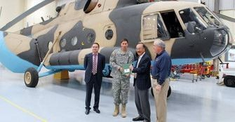 Col. Bert Vergez accepts the keys and logbook of an overhauled Russian Mi-17 helicopter from Pavel Borisov of Avia Baltika, at left, then hands them to Science and Engineering Services President Hyo Sang Lee and retired Brig. Gen. E.J. Sinclair, right, the company's CEO, during a 2012 ceremony at Redstone Arsenal. (AL.com file photo)