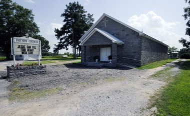 A gravel drives leads to a camp inhabited by convicted sex offenders behind Triumph Church near Clanton, Ala., on Monday, June 30, 2014. A law that took effect Tuesday, July 1, 2014 shut down the refuge, which Pastor Rick Martin says he founded to follow the Bible's instructions to care for the outcast. A prosecutor wrote a law passed earlier in the year to outlaw the camp by barring convicted sex offenders from living within 300 feet of each other on the same piece of property in Chilton County. (AP Photo/Jay Reeves)