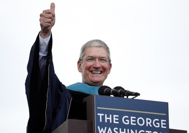 Apple CEO Tim Cook gives a thumbs up while addressing graduates during George Washington University's commencement exercises on the National Mall on Sunday, May 17, 2015, in Washington. The university awarded Cook with an honorary doctorate of public service. (AP Photo/Alex Brandon)