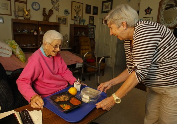 ARCHIVED PHOTO- Meals on Wheels volunteer Lynda Soberal, right, delivers a hot meal and friendly conversation to Sue Hodges (83) at the Hodges home in a Huntsville mill village Wednesday July 11, 2012. (The Huntsville Times/Glenn Baeske)