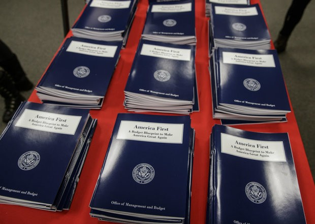 In this March 16, 2017 file photo, copies of President Donald Trump's first budget are displayed at the Government Printing Office in Washington. resident Donald Trump is proposing immediate budget cuts of $18 billion from programs like medical research, infrastructure and community grants so U.S. taxpayers, not Mexico, can cover the downpayment on the border wall.
