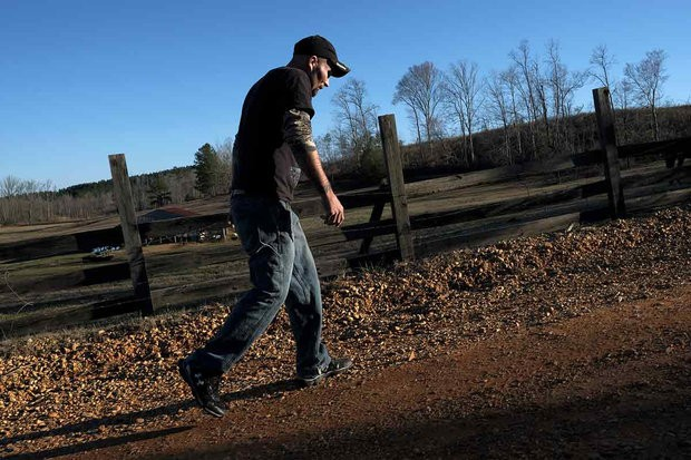 """Desmond Spencer walks near a farm where he works a few hours a week in Beaverton, Alabama. """"There's a stigma about it,"""" Spencer said, thinking about disability. """"Disabled. Disability. Drawing a check. But if you're putting food on the table, does it matter?"""" MUST CREDIT: Washington Post photo by Bonnie Jo Mount."""