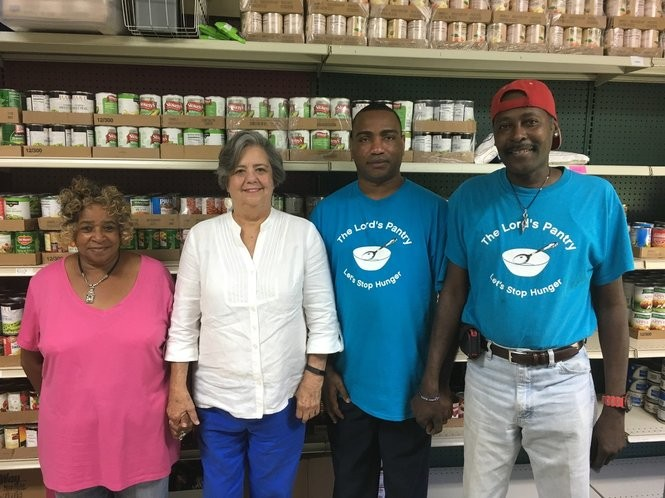 Aliceville food stamp recipients Johnnie Lindsey (left), Moses Jackson (second from right) and Ricky Minor (right) pose at The Lord's Pantry in Aliceville with the pantry's lead organizer, Marie McKinzey.