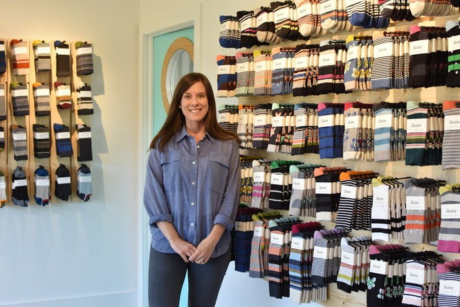 Gina Locklear stands against a wall of socks in her new storefront, The Mill Shop, at her family's sock mill in Fort Payne, Ala. Her sock lines, zkano and Little River Sock Mill, are designed and knit right in the mill.