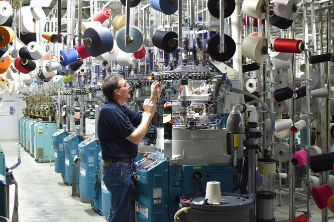 Vance Veal works on a new knitting machine that produces socks for the zkano and Little River Sock Mill brands at a mill in Fort Payne, Ala.