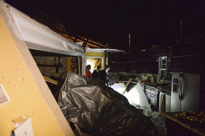 Friends and family help homeowners Michael and Phyllis Shell collect items from their home after a possible tornado destroyed it on Gatlin Road in Ardmore, Ala., Monday, March 19, 2018. Severe storms that spawned tornadoes damaged homes and downed trees as they moved across the Southeast on Monday night. (Crystal Vander Weit/The Decatur Daily via AP)