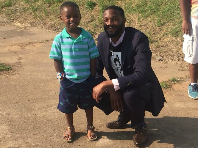 Young 'superhero' Austin Perine poses for a photograph with Birmingham Mayor Randall Woodfin Thursday after Austin donated the first $5,000 toward a new homeless shelter. Austin gives food to the homeless while wearing a red cape. (Contributed photo)