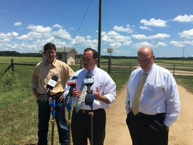 """Baldwin County Commissioner Chris Elliott (center) is joined by Commissioner Tucker Dorsey (left) and Sheriff Huey """"Hoss"""" Mack (right) at NOLF Silverhill on Thursday, June 28, 2018, to speak out against the potential to reuse the 350-acre federally-owned site as a temporary detention facility to house undocumented immigrants. (John Sharp/jsharp@al.com)"""
