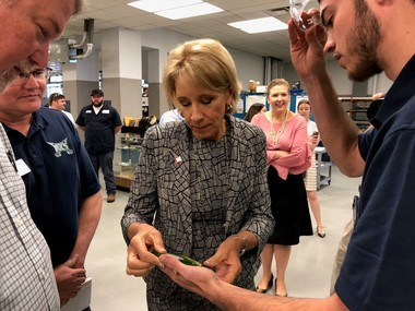 U.S. Education Secretary Betsy DeVos listens as Shelton State Community College student Harrison Hartley explains the machine process used to create the keepsake paperweight during her 'Rethink School' visit to Tuscaloosa on Oct. 4, 2018.