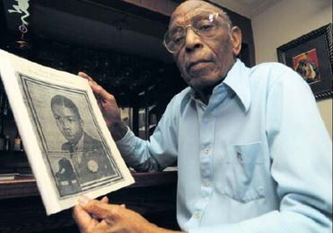 Dr. Dodson Curry holds a photo of his classmate, Julius Ellsberry in this 2010 photo. (File photo)