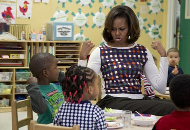 First lady Michelle Obama and a young student show off their muscles as they eat healthy snacks during her visit to La Petite Academy in Bowie, Md., last February. Obama is in the biggest fight of her tenure as she pushes back against a House Republican effort to soften a key component of the anti-childhood obesity effort at the center of her legacy. (Carolyn Kaster / Associated Press file)