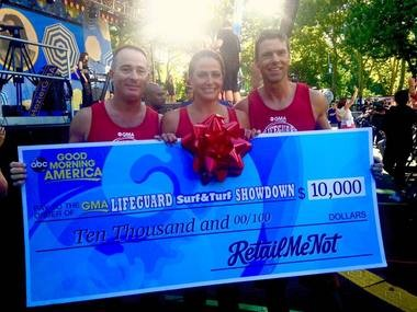 """Gulf Shores lifeguards, from left, Tony Overstreet, Brook Hopkins and Justin Pearce show off the $10,000 check they won on Good Morning America's """"Lifeguard Surf & Turf Showdown"""" on Friday, July 31, 2015. The $10,000 prize will benefit the Fire Science Academy at Gulf Shores High School. (Courtesy/City of Gulf Shores)"""