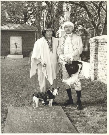 """Julian Lee Rayford, dressed as Chief Slamabamarimico and accompanied by his dog, Rosie, and Martin Johnson pose by Joe Cain's grave in the Church St. Graveyard. The photo is undated, but is likely from one of the first years after the Joe Cain Procession began in 1968. Rosie (1956-1969) was so popular that the Press Register published her photo when she died and called her """"one of the best known canines in the area."""" (Courtesy of the History Museum of Mobile)"""