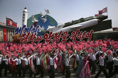 """In this Saturday, April 15, 2017, photo, North Korean men and women wave flags and plastic flowers as a float with model missiles and rockets with words that read """"For Peace and Stability in the World"""" is paraded across Kim Il Sung Square during a military parade in Pyongyang. (AP Photo/Wong Maye-E)"""