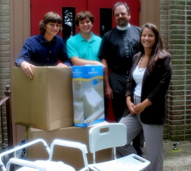Shown with some of the shower chairs being donated to needy elderly residents in the north Baldwin area are, from left, Andrew Wilson Williams Ryan Patrick Williams, the Rev. Mark McDonald, priest-in-charge at Immanuel, and Ryan Gillikin, outreach coordinator. (Courtesy Sherri Killam-Williams)