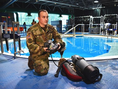 U.S. Army Staff Sgt. Michael Brown inspects his scuba gear following his underwater reenlistment at the U.S. Space & Rocket Center, Huntsville, Alabama, Aug. 31. Brown, a U.S. Army Space and Missile Defense Command/Army Forces Strategic Command Soldier, combat veteran and Wounded Warrior was introduced to scuba diving as a part of adaptive rehabilitation following the loss of his left leg in 2007 during combat operations in Iraq.