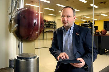 Recognized brain trauma expert Stefan Duma tests helmet impact at Virginia Tech. For the past decade, Virginia Tech players have had sensors in their helmet that measures the number of hits they take and the severity of them. (Photo courtesy of Virginia Tech)