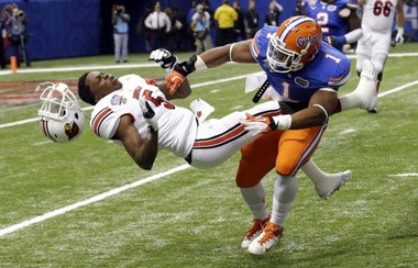 A hit by Florida linebacker Jon Bostic knocks the helmet off Louisville quarterback Teddy Bridgewater in the Sugar Bowl. Bostic was called for a 15-yard penalty on the play. (The Associated Press)