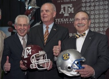 SEC Commissioner Mike Slive and Texas A&M President R. Bowen Loftin (right) give the Aggies' gig 'em sign while next to Florida President Bernie Machen after the SEC added Texas A&M in 2011.